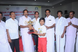 The winner S.Kabhilan from Erode  is receiving the trophy from Hon. P. Thangamani Minister for Industries and Transport.  Left Thiru. Atlas. N Nachimuthu, Chairman Kongu Educational trust, Karur and Right Thiru. N.K.M. Nallasamy, President Karur District Chess association